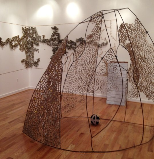 """Wings, Weavers and Worms"" (partial installation view).  The tent-like sculpture in the foreground is composed of steel wire inset with oval shapes composed of cardboard.  The rounded shapes continue on the walls.  These ovals shapes will be filled with cocoons over the next five weeks.  The white crates in the background house silkworms.  Photo by Eric Hope for East City Art."