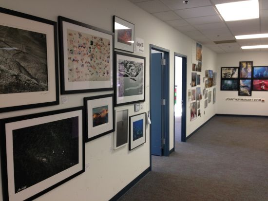 Photos hang on every vertical surface along a first floor corridor. Photo for East City Art by Eric Hope.