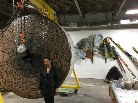 Martha Jackson Jarvis poses with a her crane holding up a work in progress.