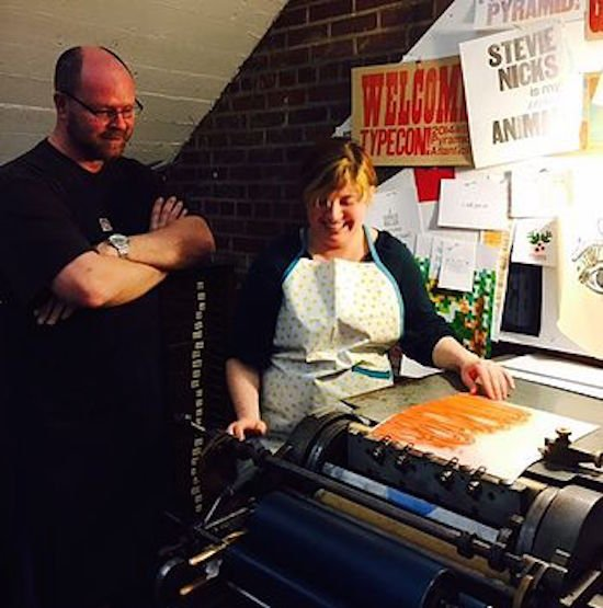 Studio intern Aleks Byrd learning to use the vandercook with James Quigley. Courtesy of PAAC.