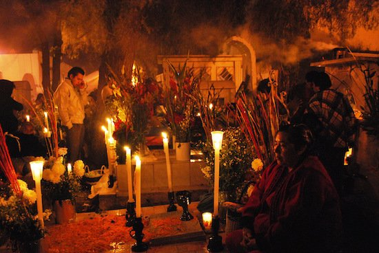 Woman by grave during the Alumbrada portion of Day of the Dead in San Andres Mixquic, Mexico City by Thelmadatter. Courtesy of WikiCommons.