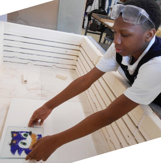 The students load the electric kiln with their artwork.