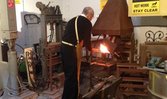 Dittmeier prepares to remove a steel rod from the forge. Photo by Eric Hope for East City Art.