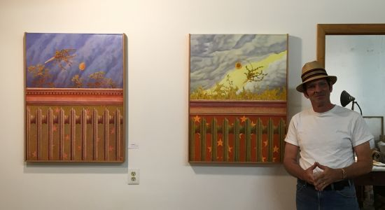 Peter B. McClintock stands with two of his quietly elegant oil paintings.