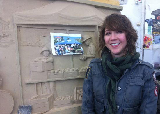 Joanna Blake poses in front of the mold for a frieze destined for Opelika, AL. Photo courtesy of Margaret Boozer.