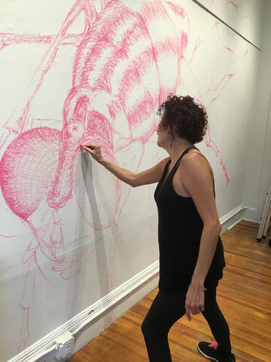 Artist Carolina Mayorga at work installing her site-specific work at the Capitol Hill Arts Workshop. Photo for East City Art by Eric Hope.